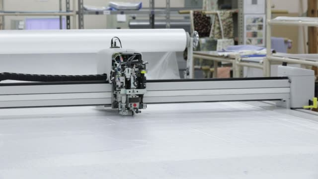 an automated flatbed pattern cutting machine cuts patterns used for making original stitch shirts at a factory operated by koyama choya sewing corp.,... - top capo di vestiario video stock e b–roll