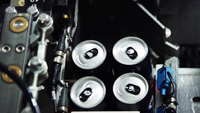eine automatisierte verpackungsmaschine bereitet aluminiumkannen für den versand und vertrieb in einer indoor-fertigung vor - getränk stock-videos und b-roll-filmmaterial