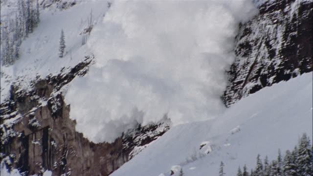 An avalanche crashes down a steep mountain.
