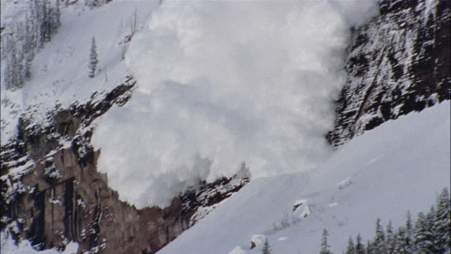 an avalanche crashes down a steep mountain. - natural disaster stock videos & royalty-free footage