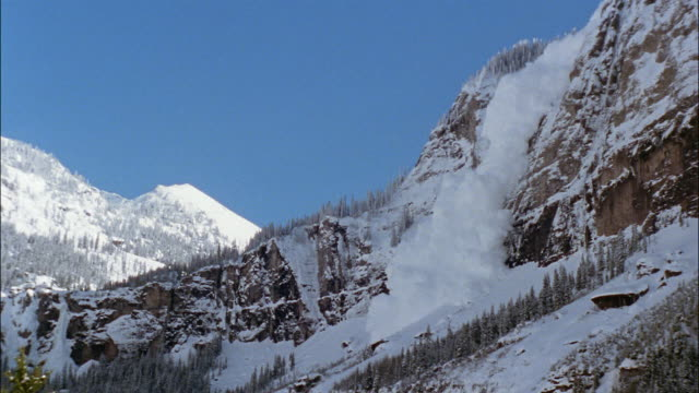an avalanche crashes down a steep mountain. - avalanche stock videos and b-roll footage