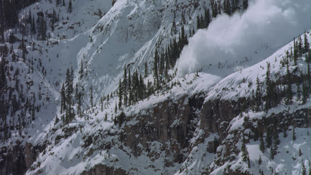 an avalanche falls down a steep mountain slope. - avalanche stock videos and b-roll footage