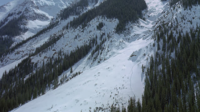 An avalanche falls down a steep mountain slope.