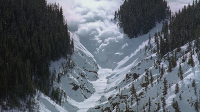 an avalanche falls down a steep mountain slope. - natural disaster stock videos & royalty-free footage