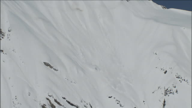 an avalanche is triggered on a steep mountain slope. - zerstörung stock-videos und b-roll-filmmaterial