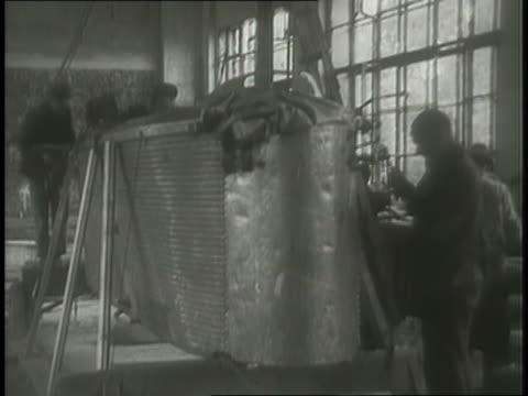 an aviation production crew assembles a gondola for a blimp inside a hangar. - hoisting stock videos & royalty-free footage