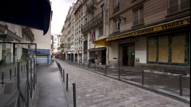an awning flaps over a storefront along a narrow parisian street. - awning stock videos & royalty-free footage