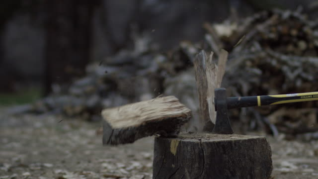 an axe chops a wooden log in half next to a woodpile at dusk - log stock videos & royalty-free footage