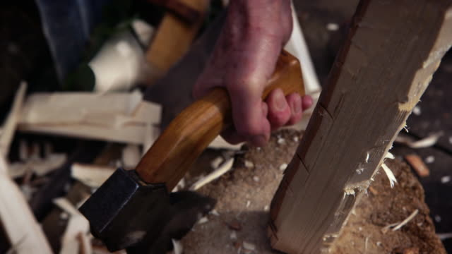 an axe is used to whittle a rough piece of wood. - wood material stock videos & royalty-free footage