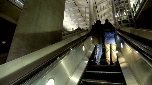 an couple ascend an escalator at canary wharf tube station in london. available in hd. - couple relationship stock videos & royalty-free footage
