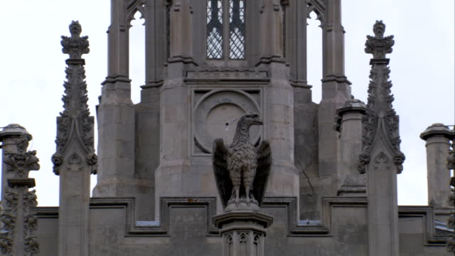 vídeos de stock, filmes e b-roll de an eagle statue perches atop the uppermost points of king's college in cambridge. available in hd. - king's college cambridge