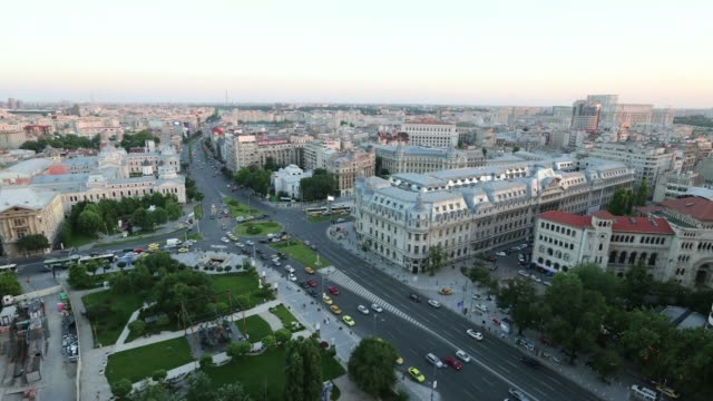 An early evening timelapse sequence shows high angle skyline view traffic driving around the University roundabout in the center of Bucharest Romania...
