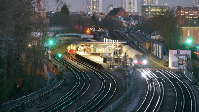an early evening view of a north london tube station platform as trains arrive and stop commuters embark and disembark - london underground stock videos & royalty-free footage