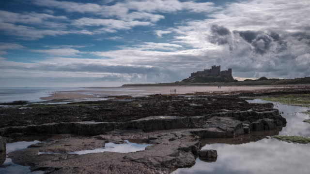 an early morning view across the rocks and beach with dramatic clouds building over bamburgh castle on the coastal shores of the north sea - northumberland coast stock videos & royalty-free footage