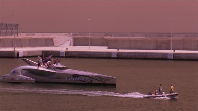 vidéos et rushes de an earthrace yacht and a raft pass a port. - chapeau de paille
