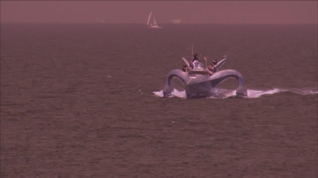 vidéos et rushes de an earthrace yacht leaves a wake near a sailboat. - chapeau de paille