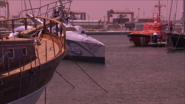 vidéos et rushes de an earthrace yacht passes between docked ships. - chapeau de paille