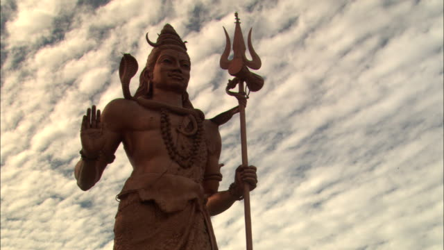 An East Indian religious statue holds a trident.