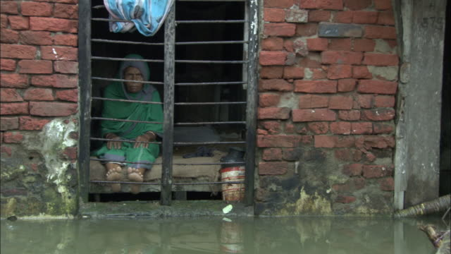 an east indian woman sits near a barred window watching the floodwaters in the streets. available in hd. - überschwemmung stock-videos und b-roll-filmmaterial