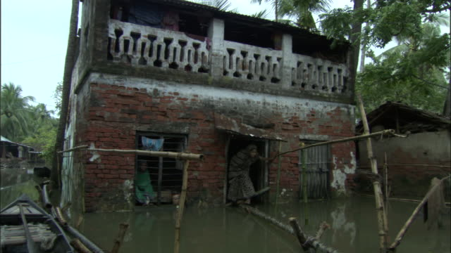 an east indian woman walks along a beam over the flooded streets in front of her home. available in hd. - bangladesch stock-videos und b-roll-filmmaterial