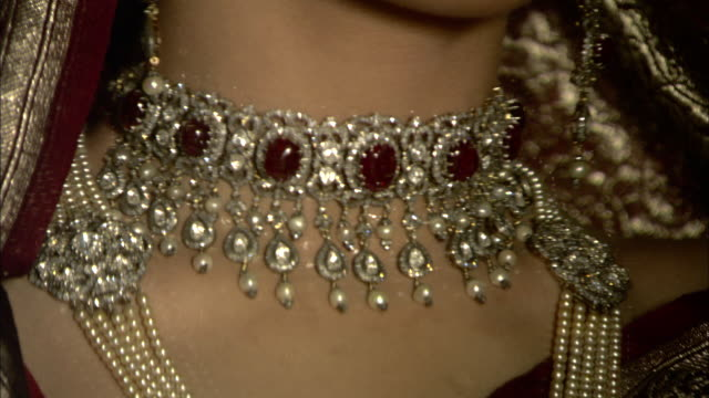 vídeos de stock, filmes e b-roll de an east indian woman wears an assortment of ruby-studded jewelry. - colar