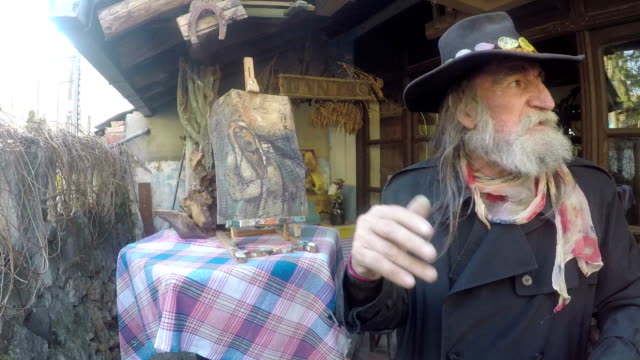 an eccentric painter in front of his studio of paintings - alternative lifestyle stock videos & royalty-free footage