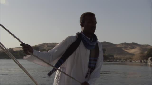 vidéos et rushes de an egyptian boater controls the sheet as he guides his sailboat in the nile river. - chapeau de paille