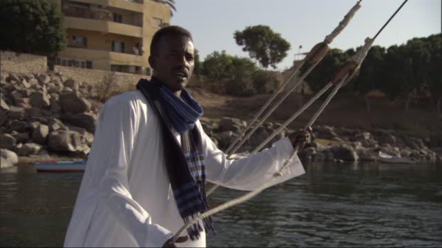 vidéos et rushes de an egyptian boater handles the sheet as he sails in the nile river. - chapeau de paille