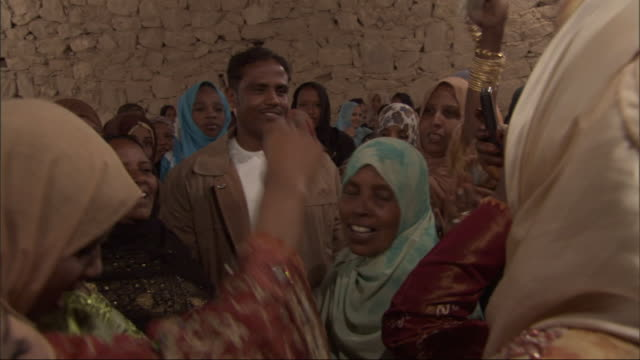 stockvideo's en b-roll-footage met an egyptian man and woman stand in the center of a crowd while everyone around them, many dressed in brightly colored burkas and head-scarves, dances, claps and waves flowers in celebration. - hoofddeksel