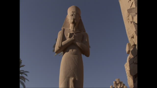 an egyptian statue of ramses presides over ancient ruins. - pharaoh stock videos & royalty-free footage