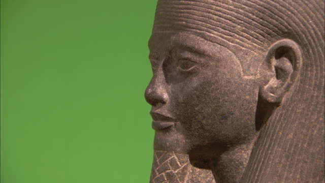 An Egyptian statue stands against a green wall.