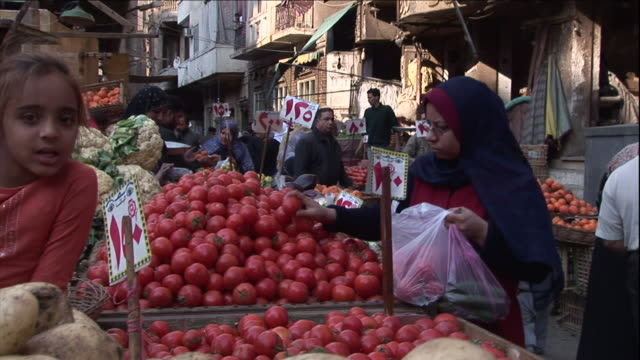 an egyptian woman in traditional clothing picks through vegetables at a street market. - モデスト・ファッション点の映像素材/bロール