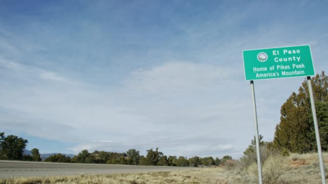 "an el paso county road sign (""home of pikes peak america's mountain"") next to a road under a partially cloudy sky in colorado - segnaletica stradale video stock e b–roll"