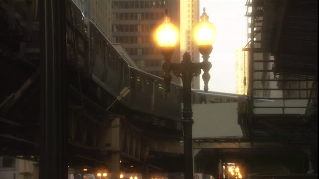 an el train travels past a lit streetlamp in chicago's downtown loop. - elevated train stock videos & royalty-free footage