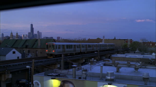 """an """"el"""" train travels past apartment buildings and warehoses. - warehouse stock videos & royalty-free footage"""