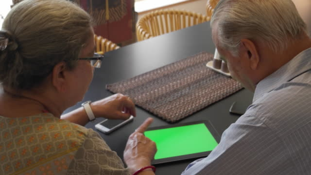 an elder couple chatting with tablet in front on the dining table, with green screen - over the shoulder stock videos & royalty-free footage