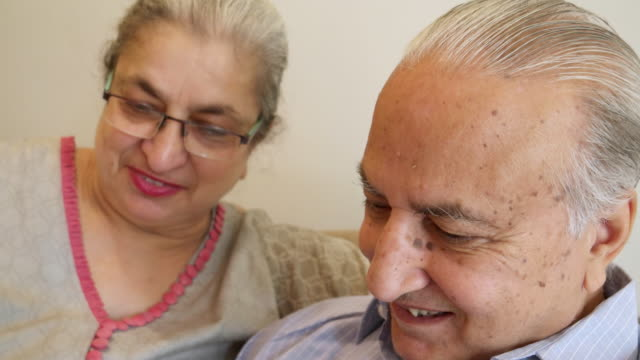 an elder couple sharing and smiling - real wife sharing stock-videos und b-roll-filmmaterial