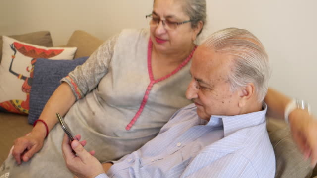 an elder gentleman shares something with his wife on a mobile device - real wife sharing stock-videos und b-roll-filmmaterial