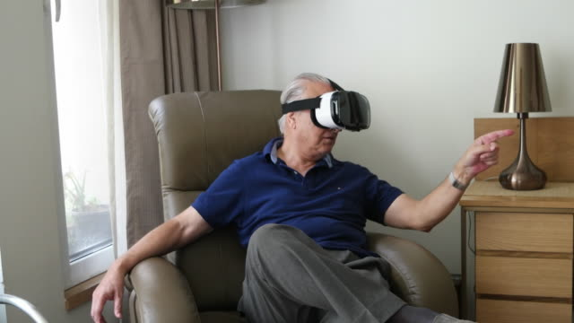an elder gentleman wearing virtual reality heat-set and speaking and trying to point at things - senior men stock videos & royalty-free footage