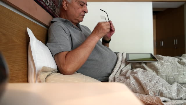 an elder indian man taking his glasses, from a sidetable, for reading on a tablet - one senior man only stock videos and b-roll footage