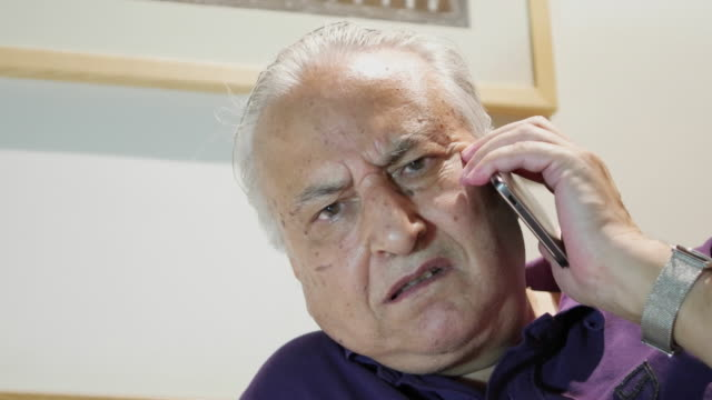 vídeos y material grabado en eventos de stock de an elder man on his mobile phone device with concerned looks - camisa de polo