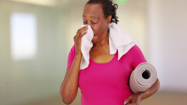 An elderly African American woman poses for a portrait as she wipes her sweat away
