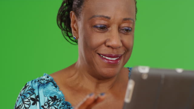 an elderly african american woman uses her tablet on green screen - maestra video stock e b–roll