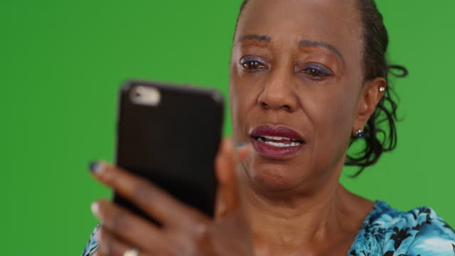 an elderly back woman swipes on her favorite dating app on green screen - maestra video stock e b–roll