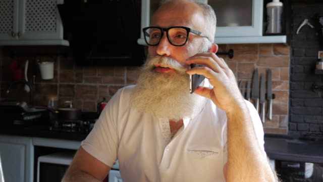 an elderly bearded man talking on the phone and smiling in the kitchen - beard stock videos & royalty-free footage