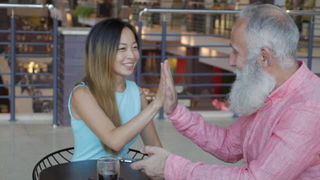 stockvideo's en b-roll-footage met een oudere bebaarde oude man en een mooie aziatische vrouw ontmoette op een winkelcentrum restaurant en het gebruik van een smartphone - ingesproken bericht