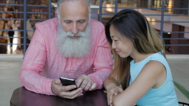 stockvideo's en b-roll-footage met een oudere oude man met baard en een mooie aziatische vrouw een smartphone gebruiken in een winkelcentrum-restaurant - ingesproken bericht
