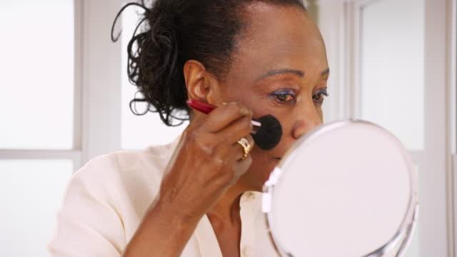 stockvideo's en b-roll-footage met an elderly black woman does her makeup in the morning in her bathroom - natuurlijk haar