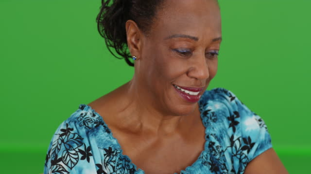 an elderly black woman looking down happily in her living room on green screen - maestra video stock e b–roll