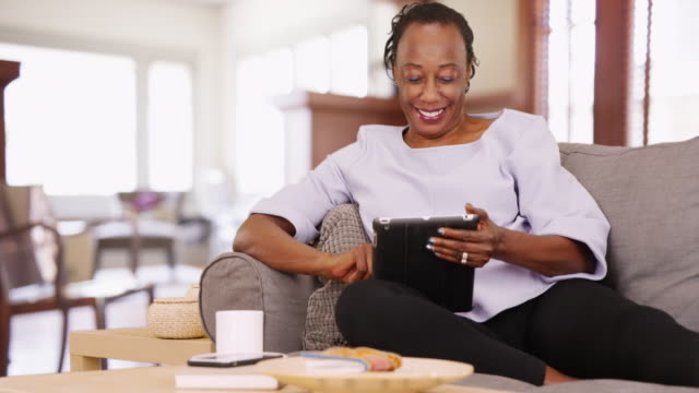 vídeos de stock, filmes e b-roll de an elderly black woman uses her tablet while relaxing on the couch - desktop pc
